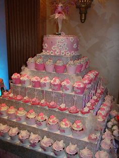 Calling all Princesses!  What a magical display.  Cupcakes in beautiful wrappers and toppers on a pyramid style tower.  Perfectly topped off with a cake and topper.  www.getcupcakepants.com