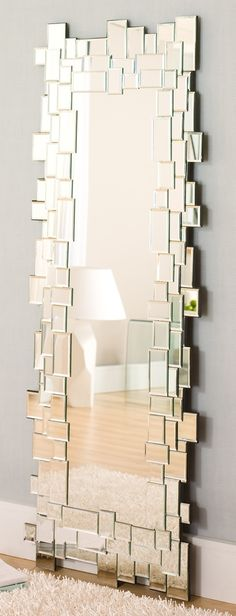 Frame out an inexpensive mirror with small mirrors, this might work with stained pieces of wood (like paint stir sticks or something)