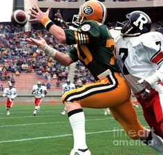 Action photograph of Edmonton Eskimos receiver Brian Kelly #70 attempting to make a catch on this play against defender Carl Brazely #7 of the Ottawa Rough Riders 1982.
