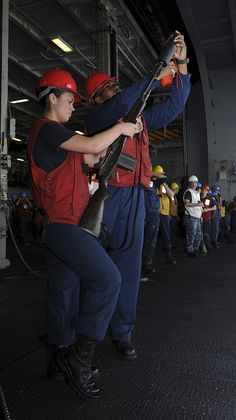 GULF OF OMAN (July 13, 2013) - Airman Megan Walker, left, of Pensacola, Fla., and Gunner's Mate 2nd Class Rylon McDuellbatiste, of Houston, get ready to shoot the line off the aircraft carrier USS Nimitz (CVN 68) during a replenishment-at-sea evolution. Nimitz Strike Group is deployed to the U.S. 5th Fleet area of responsibility conducting maritime security operations, theater security cooperation efforts and support missions for Operation Enduring Freedom