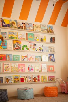 Playroom book wall and orange striped ceiling