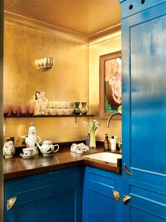Hannah Gurney, a director for De Gournay, is anything but boring with color in her London home. The kitchen features gold-leafed walls, mahogany countertops, and peacock blue cabinetry—a combination that helps to enlarge and brighten the otherwise petite space.
