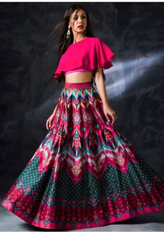 A multicoloured lehenga with abstract print in the shades of turquoise blue and fuschia pink. Moreover, teaming it with a unique cape-style hot pink blouse gives the outfit a perfect finishing. Hot Pink Lehenga with abstract print Indian Gowns Dresses, Indian Fashion Dresses, Indian Designer Outfits, Bridal Dresses, Choli Designs, Lehenga Designs, Lengha Design, Lehnga Dress, Lehenga Choli