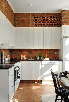 Wine cubbies built into the exposed-brick kitchen wall.