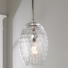 """Dimpled Glass Pendant Dimpled clear glass and chrome hardware brings this contemporary pendant to life. Hangs from chrome rods for a sophisticated look. (1) 6"""", (2) 12"""" chrome rods, 5"""" chrome round canopy and 48"""" of cord supplied. (12""""Hx7""""W)."""