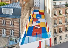 A multicoloured basketball court has been tucked between a row of traditional Parisian apartments.