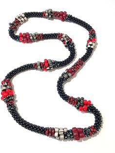 Red & Black Mix Necklace by Sher Berman. Bold red mixes with black to make a statement necklace. Indonesian, African white hearts, Czech, and Japanese glass beads have all been strung on cord and then crocheted one at a time with a crochet hook.