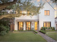 Custom | white painted brick mixed with stucco + front door design mimics the French doors | Houston TX West University Festival of Homes