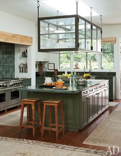 The kitchen of Ellen DeGeneres and Portia de Rossi's Beverly Hills home has an artisanal, Arts and Craft–like design aesthetic, thanks in part to the custom-made hanging glass display case that serves as storage for tableware. The stainless-steel range is by Wolf, and the green tile backsplash and painted cabinetry offset the neutral tones of the barstools and antique rugs. The rustic floor is crafted of reclaimed teak beams