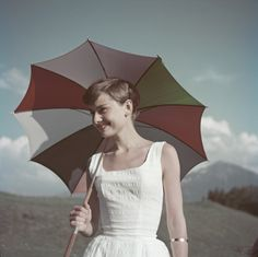 Applying sunscreen is a key step in any anti-aging beauty routine, but if you want an extra means of protection, a colorful umbrella like the one Audrey carried on a beach in 1955 is stylish and functional.  - GoodHousekeeping.com