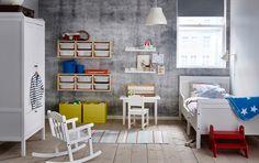 Kinderkamer met uittrekbaar bed, garderobekast, schommelstoel, tafel en stoel, allemaal in wit