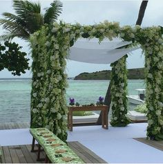 O altar da cerimônia de Helena Bordon e Humberto Meirelles em St Barths: tenda de flores, tapete branco sobre deque de madeira e bancos com leques para convidados. A decoração foi regida pelas cores verde e branco.