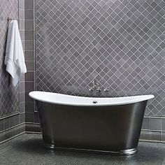 A simple pattern adds interest to this gray tile wall. 3x3 tiles set on the diagonal framed by 6x6 tiles and moulding.