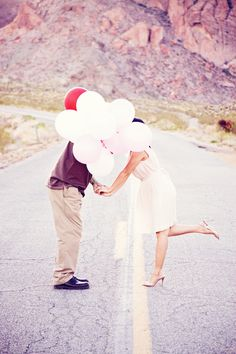 Hidden couple kiss, with balloons!  Love the cutesy foot lift!  Photograph by Moxie Studio