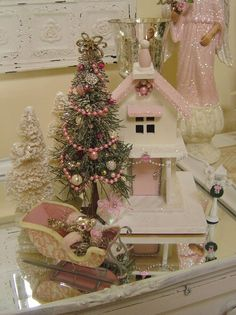 .Pink and white putz building with sleigh and decorated bottle brush tree.