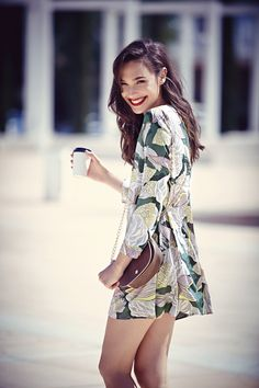 Gal Gadot in a long sleeve floral print dress with a brown leather crossbody purse