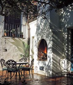 Patio, Montecito Spanish Colonial by Architect Thomas Bollay. a charming outdoor living space complete with the ambiance of a wood-burning fireplace.