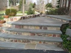 The surface is wet-set Pennsylvania pattern flagstone; the sides and fronts of the steps are natural stone veneer; and the steps and landings are capped with flagstone treads. #hardscaping #masonry #flagstone