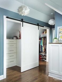 A barn-style door hangs in front of the two-compartment closet and slides open as needed. The suite's large closet is divided into two zones. Half the closet accommodates hanging clothes while the other side caters to folded clothes with built-in drawers and display space for accessories on top.