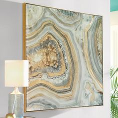 Mineral, vegetable or art? Our Marble Artwork blows up the natural beauty of a complex mineral to reveal a swirling world of blues and golds. Applied gold foil gives the artwork an added layer of texture and an added element of design. Not to mention bling. A gold floater frame completes the look. Rock on.                Canvas artwork with zoomed photographic image of an agate                    Exacting print with stunning details and colors                    Canvas mixture of plastic…