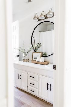 A transitional bathroom designed with a black round vanity mirror, a white washstand with matte black hardware pull. The greenery in a glass vase, natural wood towel bowl and framed photo warm the room just perfectly. White Vanity Bathroom, Small Bathroom, Mirror Vanity, Round Mirror In Bathroom, Master Bathroom, White Bathroom Decor, Modern Bathroom, Black Round Mirror, White Bathroom Cabinets