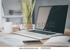 Comfortable working place. Close-up of comfortable working place in office with wooden table and laptop laying on it