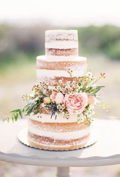 Naked Wedding Cake with Pink Flowers and Greenery. A country-chic naked wedding cake by Sprinkle