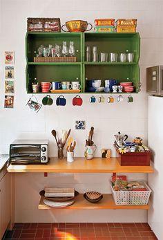 Caixotes de frutas pintados com tinta esmalte (Capim Limão, da Suvinil) criam um armário.