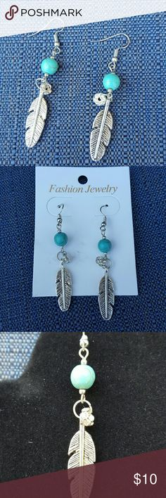 "Cute feather earrings Great pair of feather earrings.  Go with everything.  Silver tone with turquoise bead.  Little bit of bling with a dangling crystal above the feather.  Measure about 3"" fron the top of the bale. Jewelry Earrings"