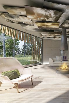 Old and modern architecture merge to create the design of this rustic house set in a forest in Ireland.  Inspired by the historical Celtic roundhouse the exterior structure is shrouded with a wood trellis-style cladding to create the conical round shape. The interior design is minimal with concrete walls, modern furniture, colorful artwork and accessories.  | #livingroom | #fireplace | #art |