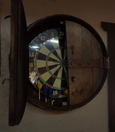 Dart board cabinet is made from wine barrel or whiskey barrel ends. Doors open and each side is painted with chalkboard paint to keep score. Perfect for any game room or bar. Dart Board Backboard, Dart Board Cabinet, Whiskey Barrel Furniture, Custom Dart Board, Pool Table Room, Automotive Decor, Automotive Furniture, Barrel Projects, Fire Pit Furniture