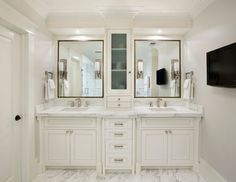 Master bathroom features his and her washstands topped with white marble countertops and black framed mirrors flanking center console cabinet over white and gray marble floor.
