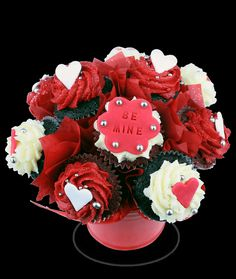 The Small Valentines Day Theme Mini Cupcake Bouquet - Consisting of 7 assorted mini valentines themed cupcakes. Cupcakes include a combination of chocolate and red velvet cakes, with a combination of red butter cream and white cream cheese icing with a combination of our valentines themed mini cupcake toppers.