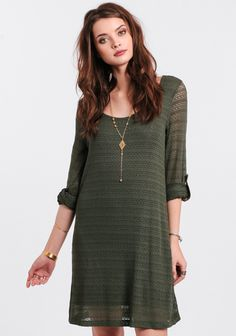 Olive-green knit dress with a shift silhouette and sheer sleeves with optional roll-tabs. Accessorize it with layers of necklaces and knee-high boots for hanging with the girls.