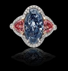 Long Oval Fancy Vivid Blue Diamond (nearly 3.5 carats). Ring includes two Fancy Intense Argyle Pink Diamonds