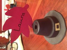 Happy Thanksgiving! My sister and I made these cute little pilgrim hat place holders a few years ago and we use them every Thanksgiving.  1. Spray paint little flower pots black.  2. Cut out circles out of black felt and glue to flower pots upside down to the felt.  3. Cut out tiny yellow construction paper squares, color a square in the middle black, and glue it to the front of the pot.  4. You can't see it in this picture but I have a tiny clothes pin glued to the back of the pot to hold…