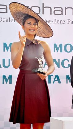 Jacqueline Fernandez posing for the shutterbugs with the trophy at a horse racing event.