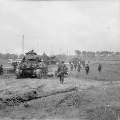 Infantry of 3rd Division move inland from Queen beach, Sword Area, past a Sherman tank of 27th Armoured Brigade, 6 June 1944