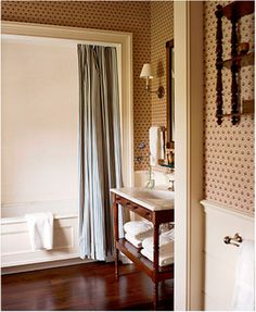 This traditional bathroom has a medallion wallpaper above a cream colored beadboard—both very East Coast style interior design elements. The furniture style vanity feels like an antique.