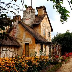 Marie Antoinette's cottage at Le Hameau, Versailles:  the thatched-roof Disneyland-style farm where the queen and her ladies-in-waiting indulged the fashionable fantasy of ``returning to nature,'' dressing up as milkmaids and shepherdesses.
