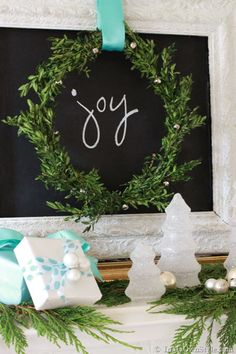 Beautiful white and aqua mantel with greens.  LOVE the glittered glass trees and chalkboard!