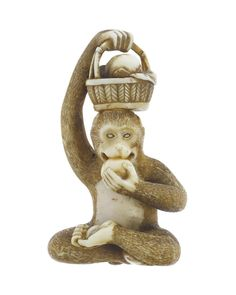 Netsuke of carved ivory, a monkey sitting holding a basket of fruit on its head with its right hand and eating fruit with his left hand, unsigned: Japan