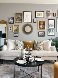 Eclectic glam living room with a white velvet sofa and gallery wall | round black coffee table adds a graphic element | Classic howard style velvet sofa | IKEA Stocksund sofa with a Bemz cover in Eggshell Zaragoza Vintage Velvet from Designers Guild