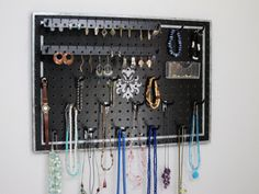 This hanging jewelry organizer board has an elegant design in silver on a satin black background.   Arrange the hooks, earring holders, and clear basket however you like!  Long hooks hold multiple necklaces, bracelets, rings, and more. Jewelry Organizer  by JansJewelryOrganizer, $47.95