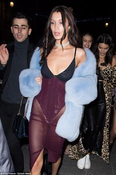 Dazzling: The garment featured a black thong bodysuit with a sheer purple skirt, and keeping her favourite accessory of the evening, she layered up in a fluffy blue stole