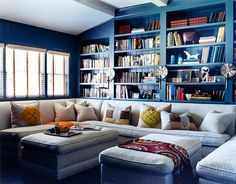 HB I forget who did this but love it all - the colors, bookcase arranging- big built in sofa and matching ottomans. Love the sconces - love this all!!!