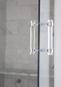 A glass walk-in shower door fitted with a distinctive Lucite handle from LuxHoldups opens to a walk in shower lined with white and gray marble wall tiles that extend to a marble shower bench.