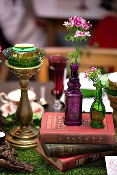 Glowing jewel toned glass and vintage books for a woodland themed wedding tablescape.  View the full whimsical Alice in Woodland Tea Party Wedding Styled Shoot on SingaporeBrides.