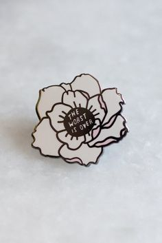 "1"" wide pin in white & pale pink hard enamel and polished black metal."
