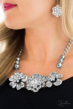 Abloom -Strands of bulky silver chain and polished silver beads give way to three flower frames below the collar. Brushed in lifelike floral detail, the glistening flowers feature glittery rhinestone centerpieces for a timeless finish. Features an adjustable clasp closure.
